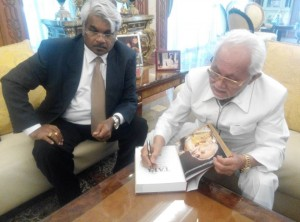 Pehin Seri Taib signing the book written about him by the author, Mr Siva Kumar G at a private autograph signing session.